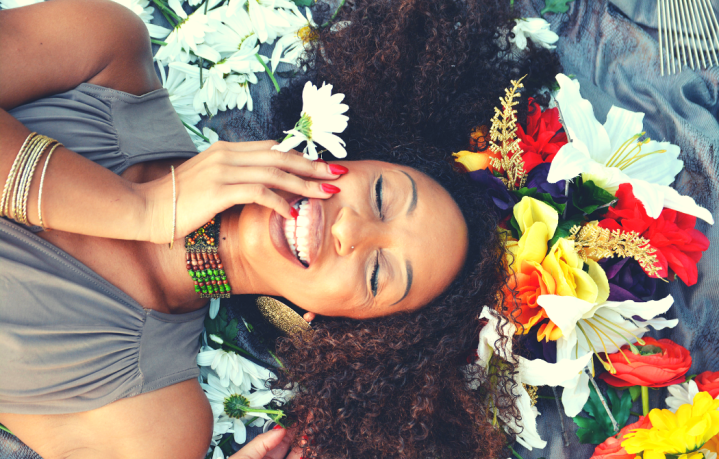 4 Affirmations to Change Your Life Featured Image with Black Woman Smiling in Flowers