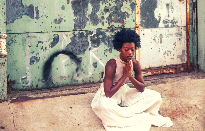 How Mindfulness Meditation Changed My Life Featured Image with Black Woman Wearing Afro Meditating