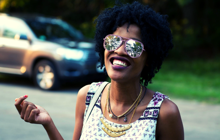 10 Ways to Get Through Depression Featured Image with Black Woman with Fro Wearing Smiling In Sunglasses in Purple